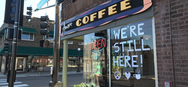 "Sign in the window at Amore Coffee: ""We're still here!"""