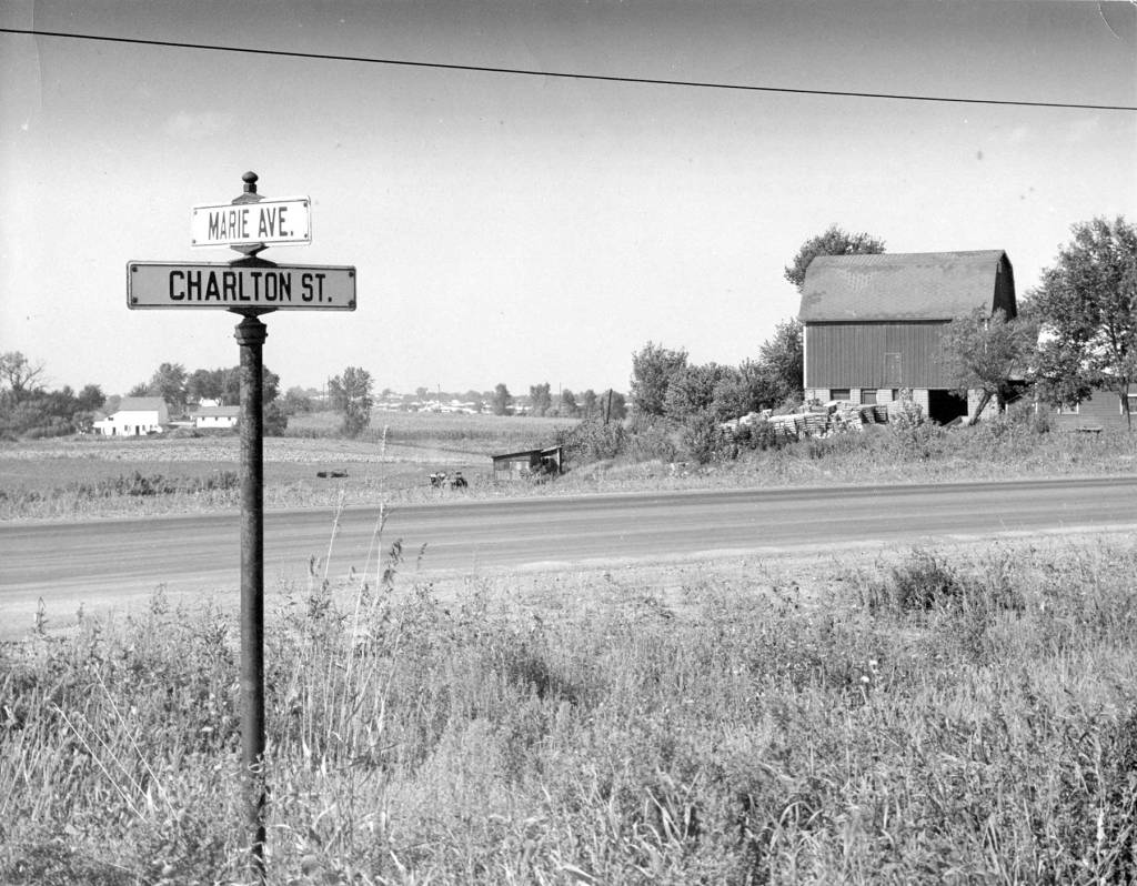 Marie and Charlton intersection in 1961 with a street sight in the foreground and a barn in the background.