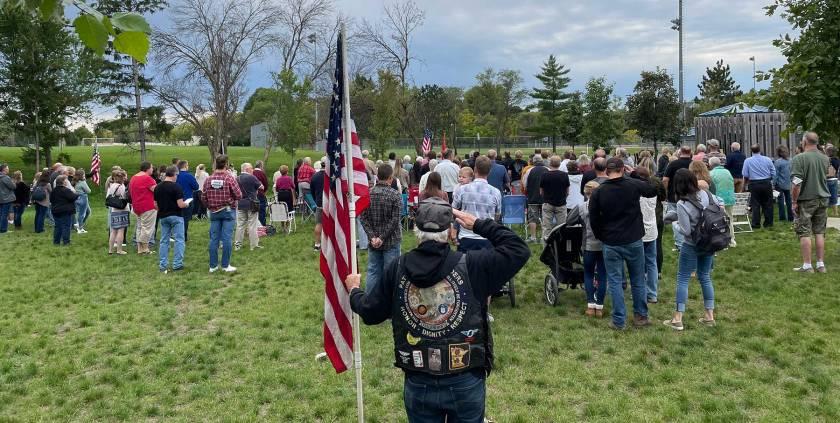 Crowd standing for national anthem at Joseph Marthaler Memorial Bridge dedication ceremony.